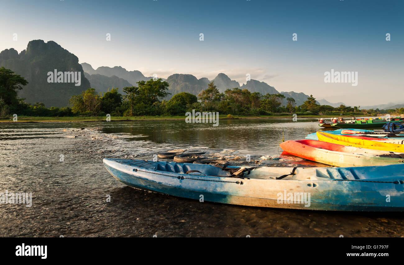 Kayak et bateaux longtail dans la rivière Nam Song à Vang Vieng, Laos Photo Stock