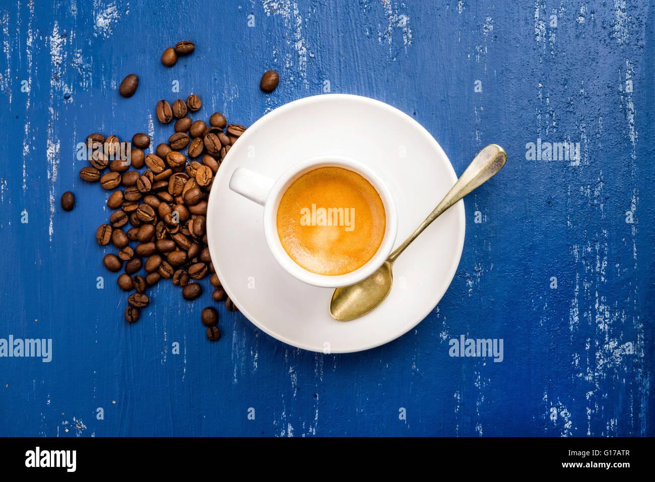 Tasse de café espresso et de haricots sur la table en bois peint bleu arrière-plan. Vue d'en haut, Photo Stock
