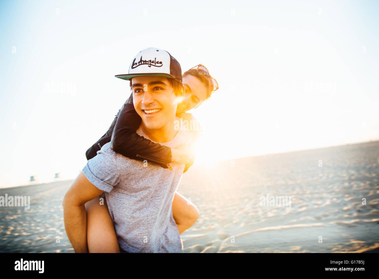 Young man giving girlfriend a piggy back sur la plage ensoleillée, Venice Beach, California, USA Photo Stock