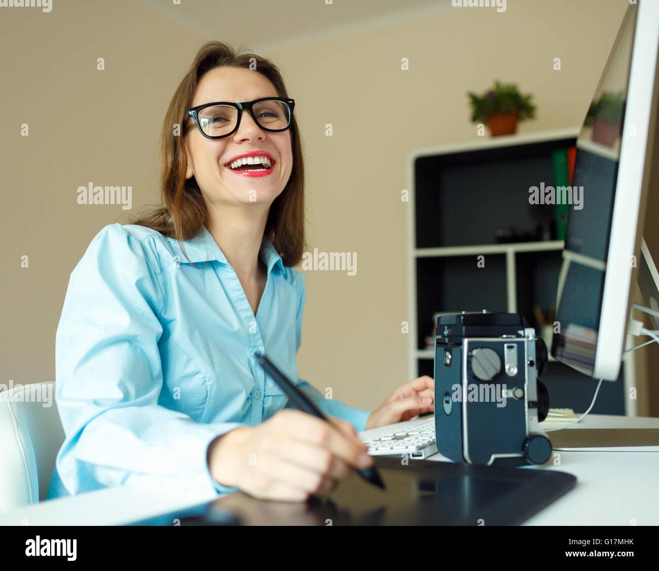 Jeune femme dessin artiste quelque chose sur tablette graphique au home office Photo Stock