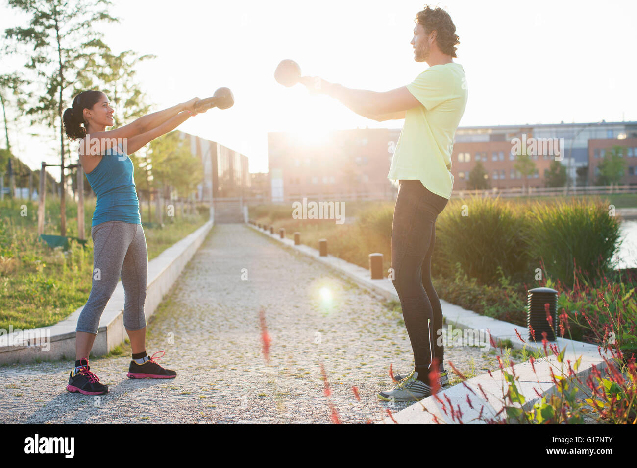 Femme et entraîneur personnel la formation de poids avec kettlebells à Riverside Photo Stock