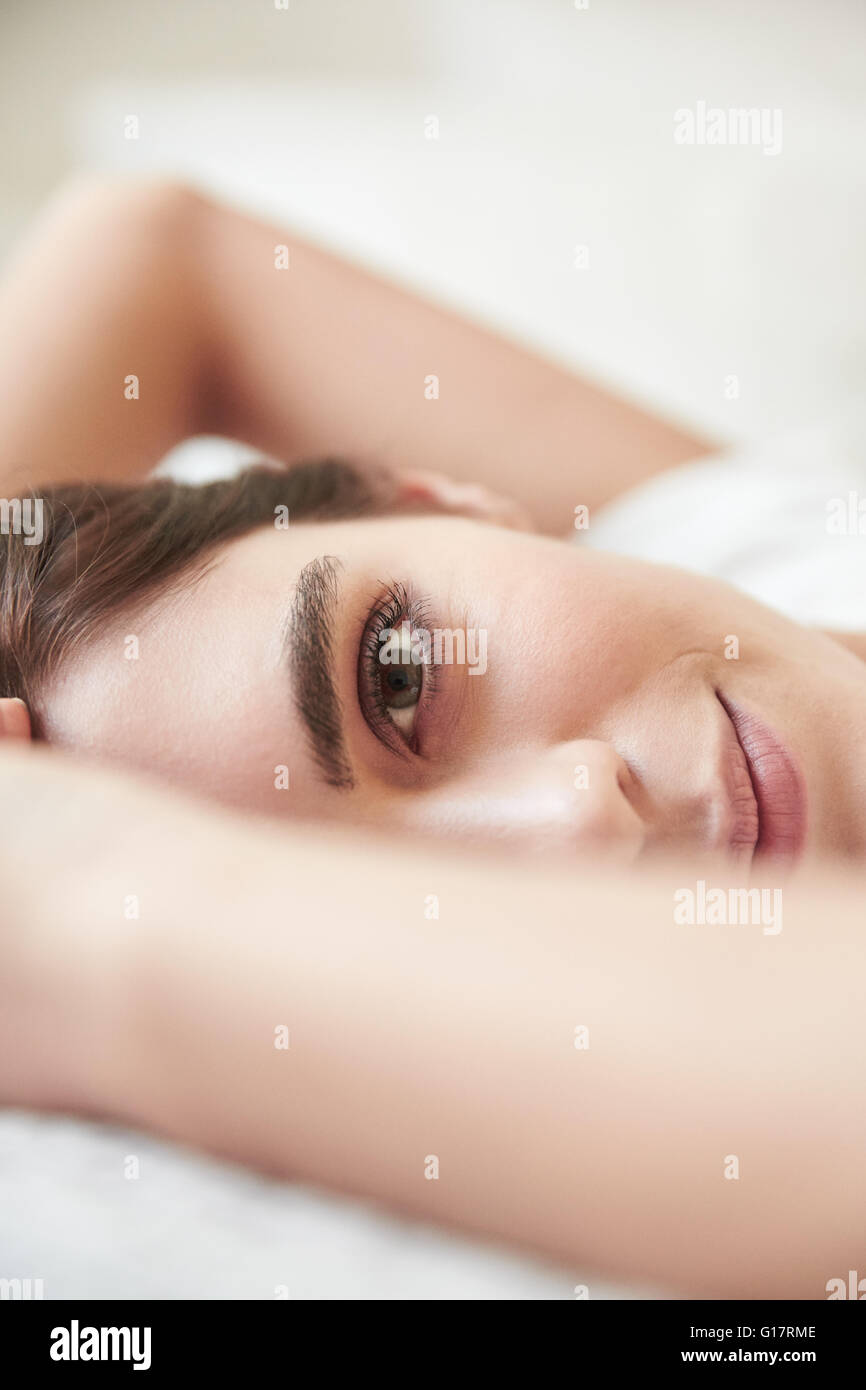 Close up portrait of beautiful young woman lying on bed Banque D'Images