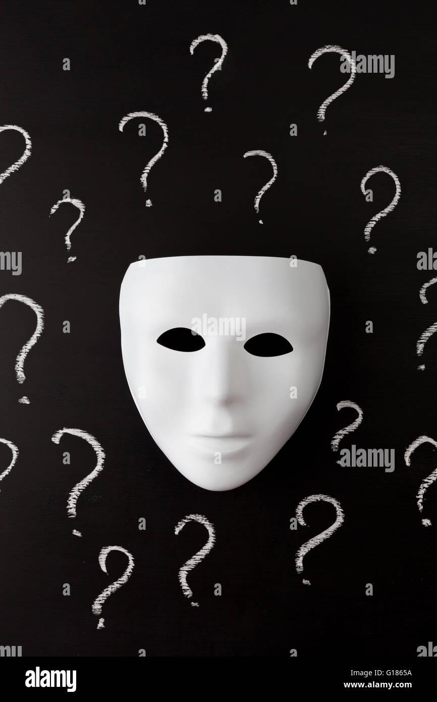 Masque Blanc sur fond noir avec de la craie à la main d'interrogation. Qui suis-je? Concept d'identité. Vertical Banque D'Images