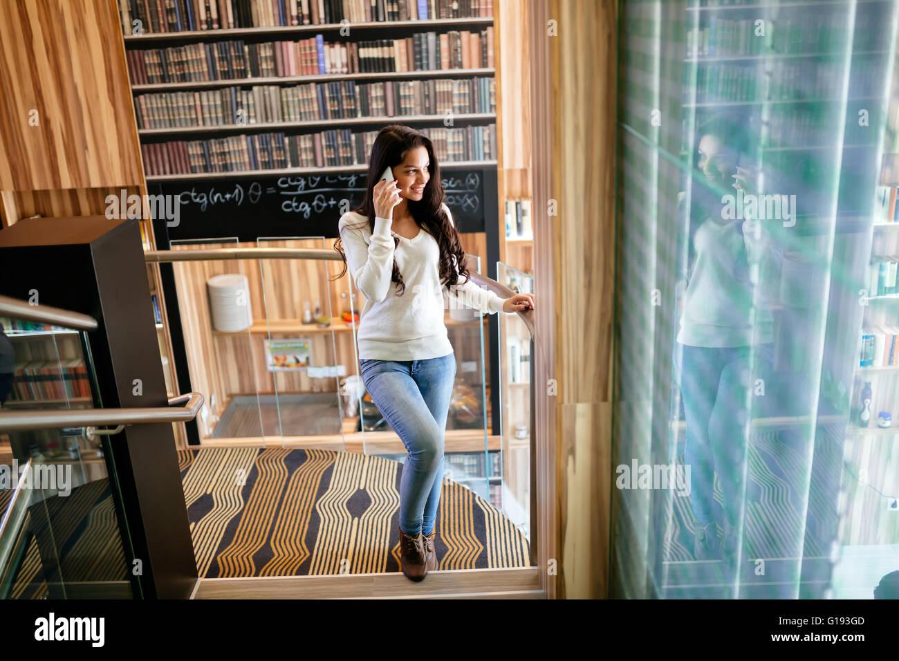 Businesswoman using phone intérieur et smiling Photo Stock