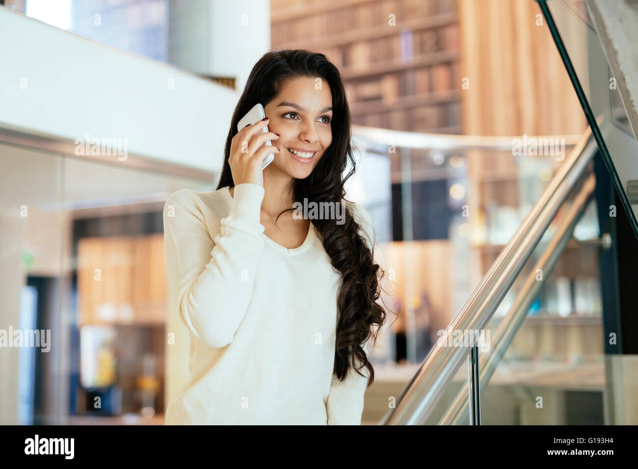 Businesswoman using phone intérieur et smiling Banque D'Images