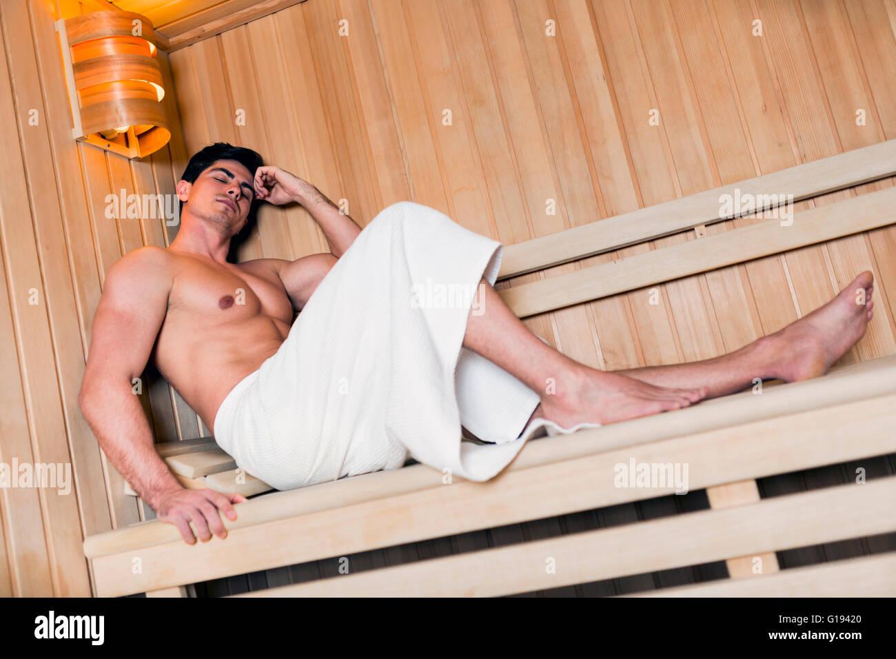 Handsome man relaxing in a sauna avec une serviette enroulée autour de la taille Photo Stock