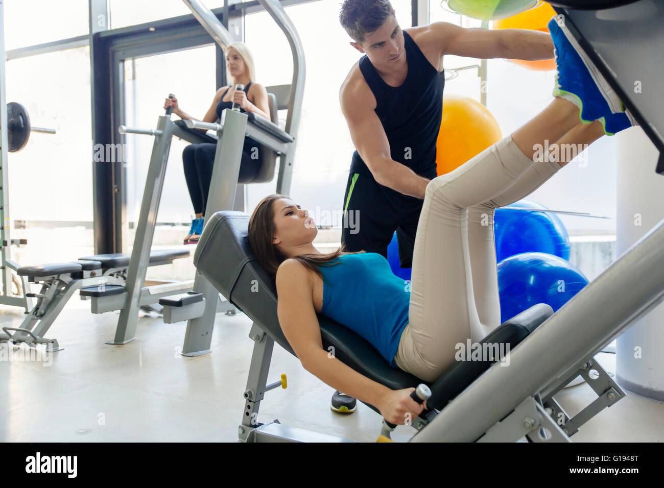 Belle femme faisant les jambes dans une salle de sport avec l'aide de l'entraîneur personnel Photo Stock