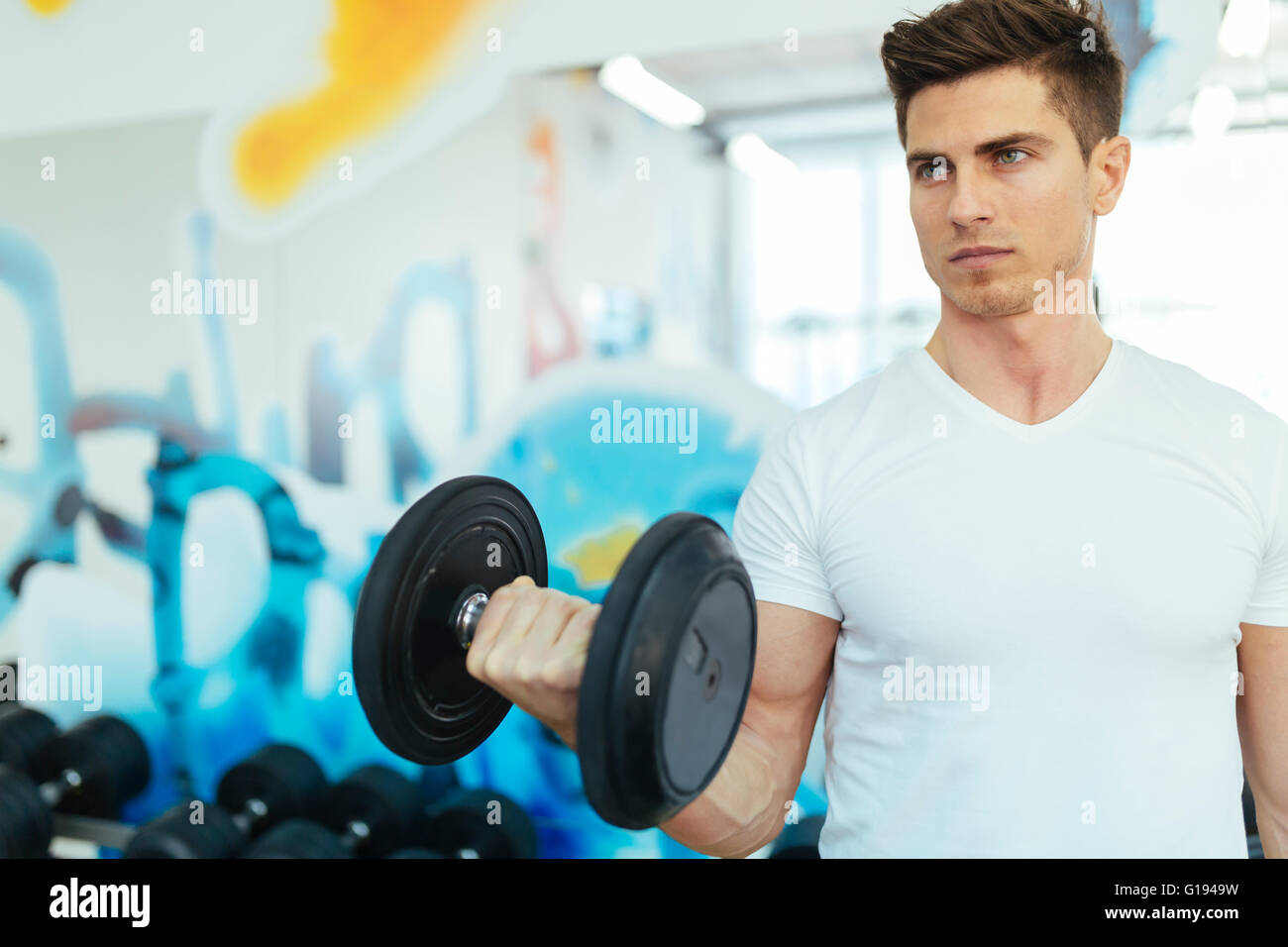 Handsome man lifting weights in gym et demeurer en forme Photo Stock