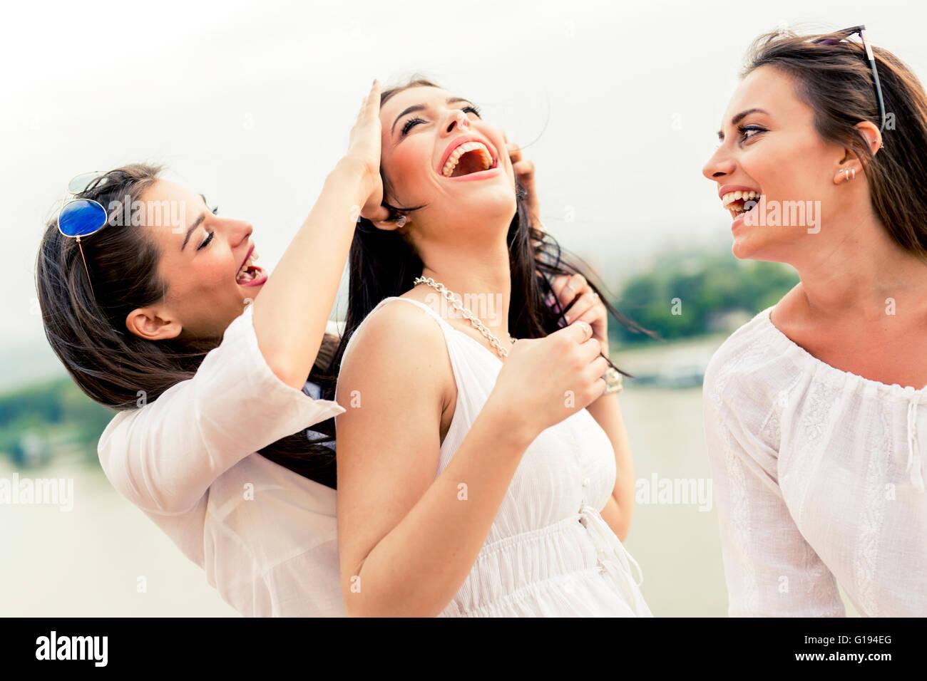 Les femmes gaies s'amuser en plein air et de rire heureusement Photo Stock