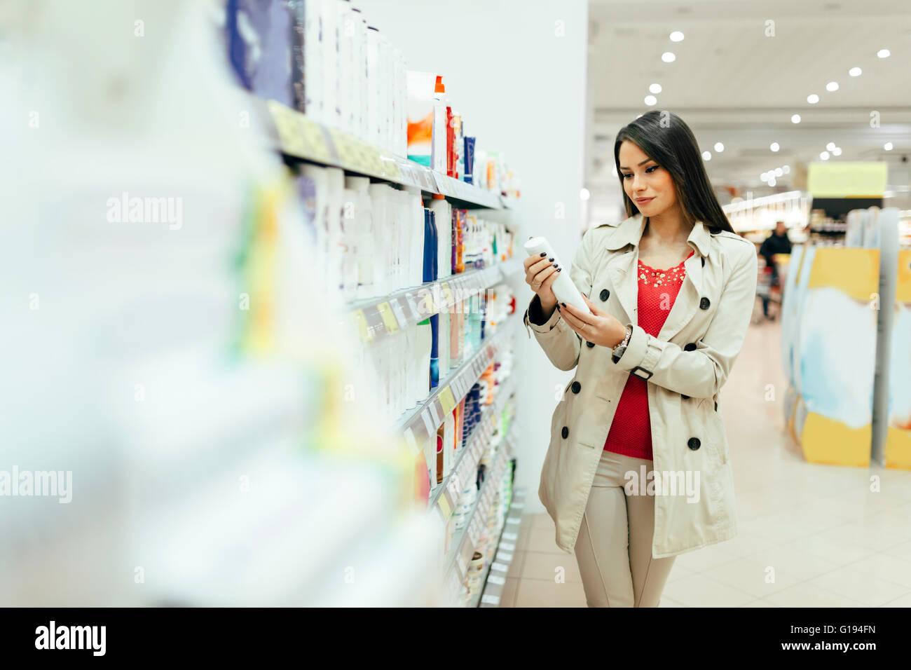 Belle femme l'achat de produits pour les soins du corps en supermarché Photo Stock