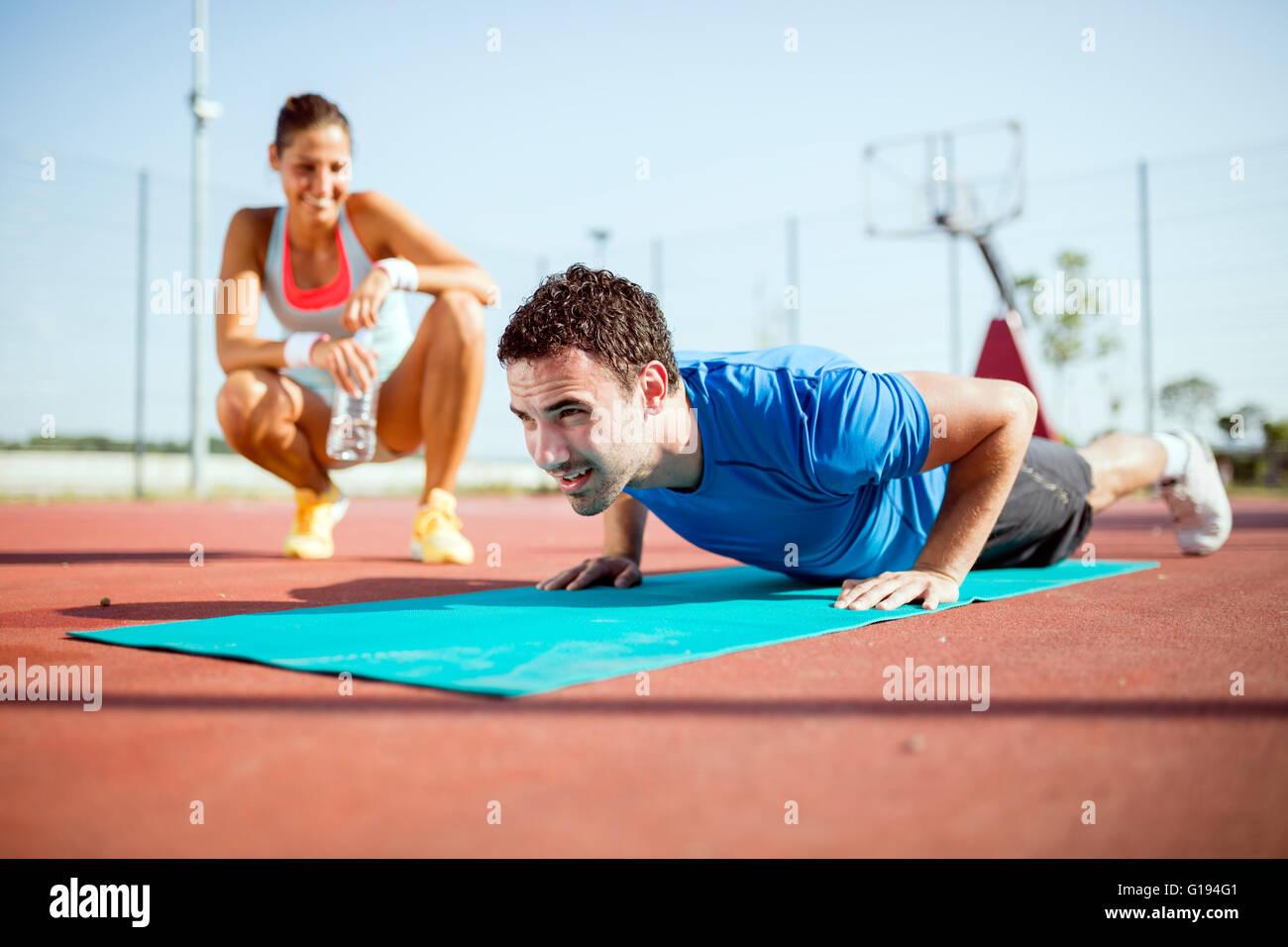 Jeune, belle, en forme et en bonne santé l'entraîneur personnel comptant push-ups et motivant Photo Stock