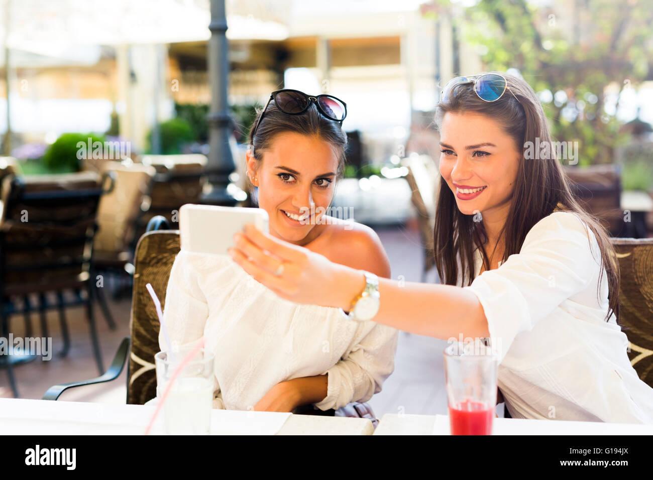 Deux belles jeunes femmes prenant une des selfies eux-mêmes pendant la pause déjeuner Photo Stock