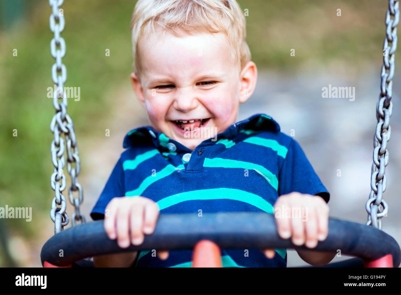 Enfant espiègle sur swing outdoors smiling cordialement Photo Stock