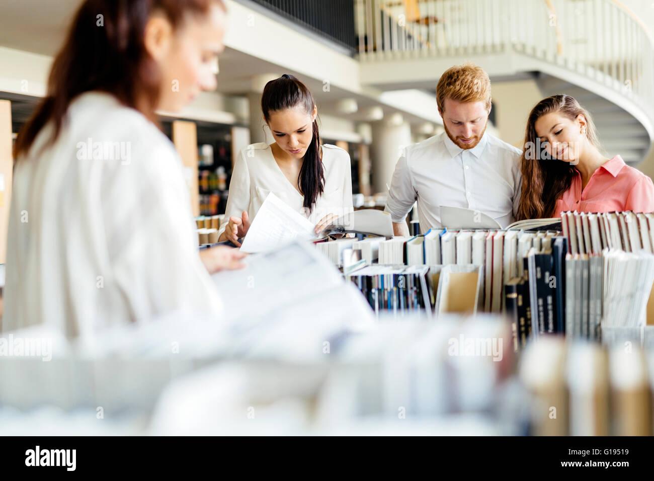 Groupe d'étudiants qui étudient en bibliothèque et la lecture de livres Photo Stock