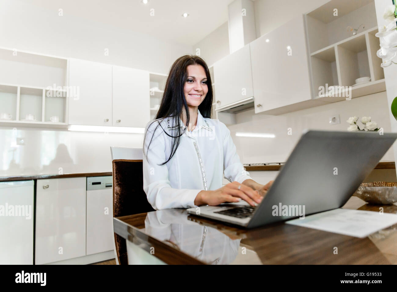 Belle brune qui travaillent sur un ordinateur portable dans sa belle maison Photo Stock