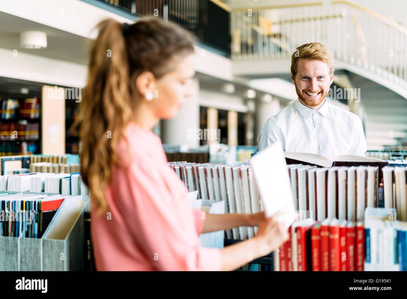 Belle heureux les étudiants qui étudient et flirter dans une bibliothèque moderne Photo Stock