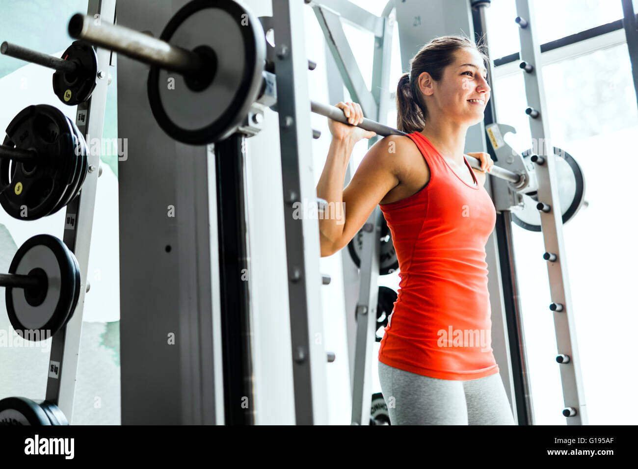 L'accent young Beautiful woman lifting weights in a gym Photo Stock