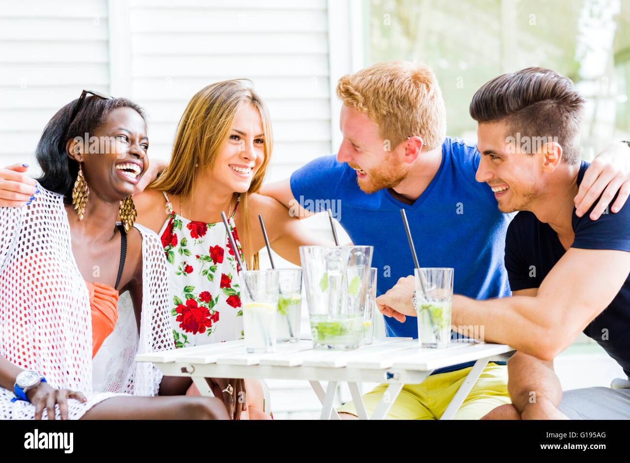 Les amis de rire et s'étreindre chaque origine à l'extérieur et être heureux Photo Stock