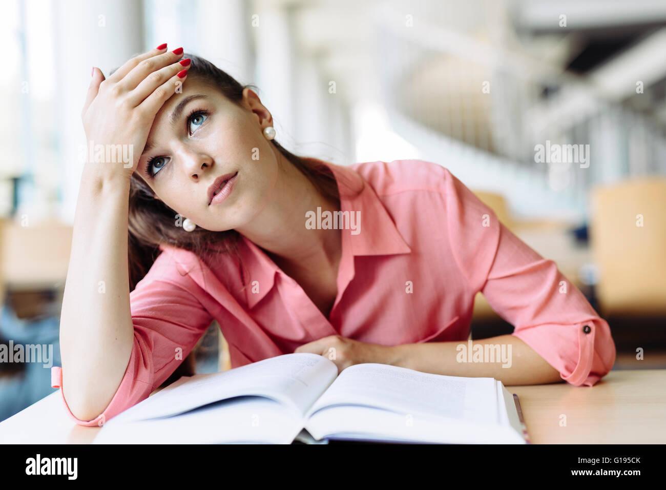 Étudiante l'étude et la lecture dans une bibliothèque, mais a du mal à comprendre le contenu Photo Stock
