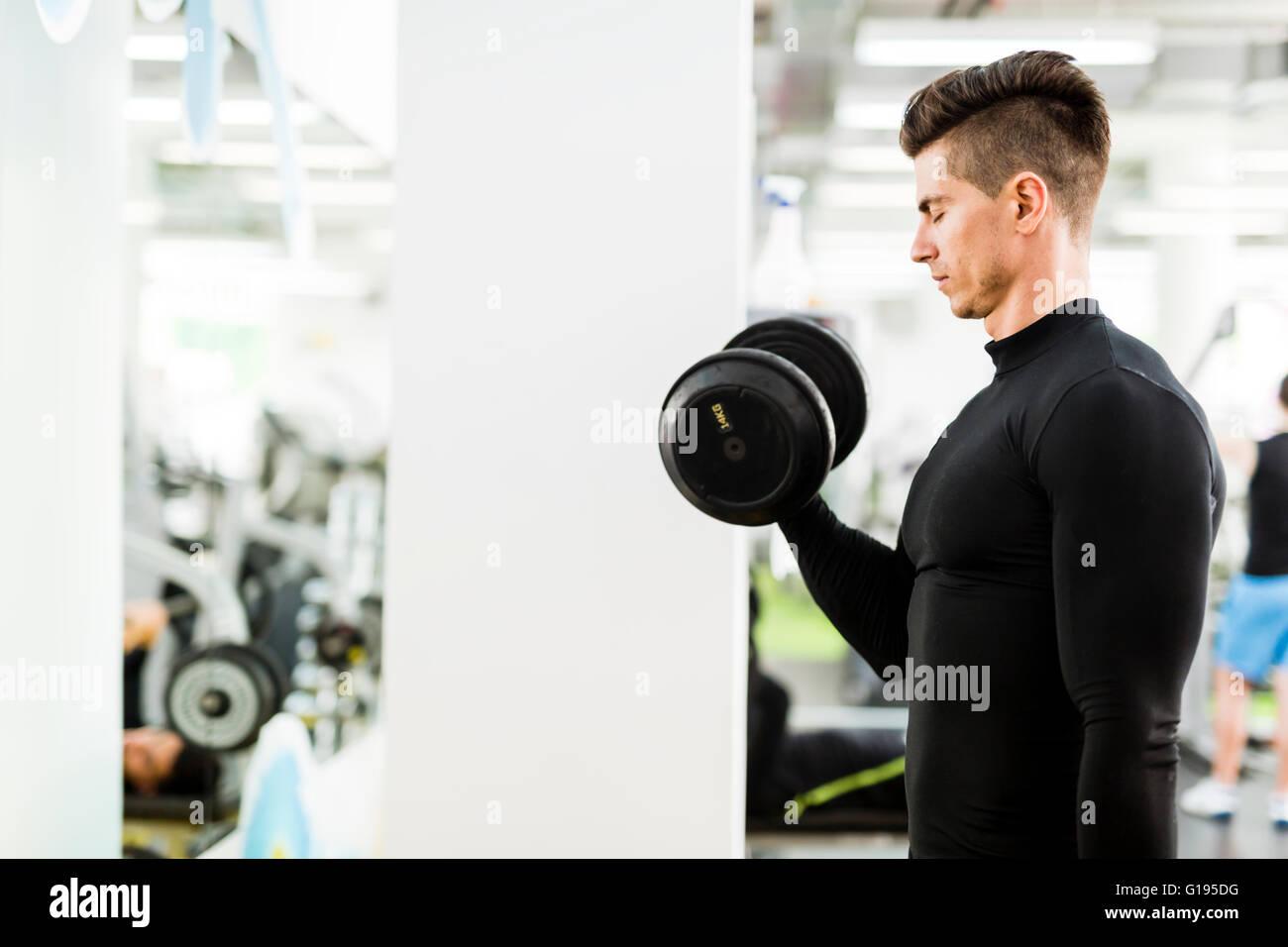 Beau jeune homme qui travaille dans une salle de sport et la levée de poids Photo Stock
