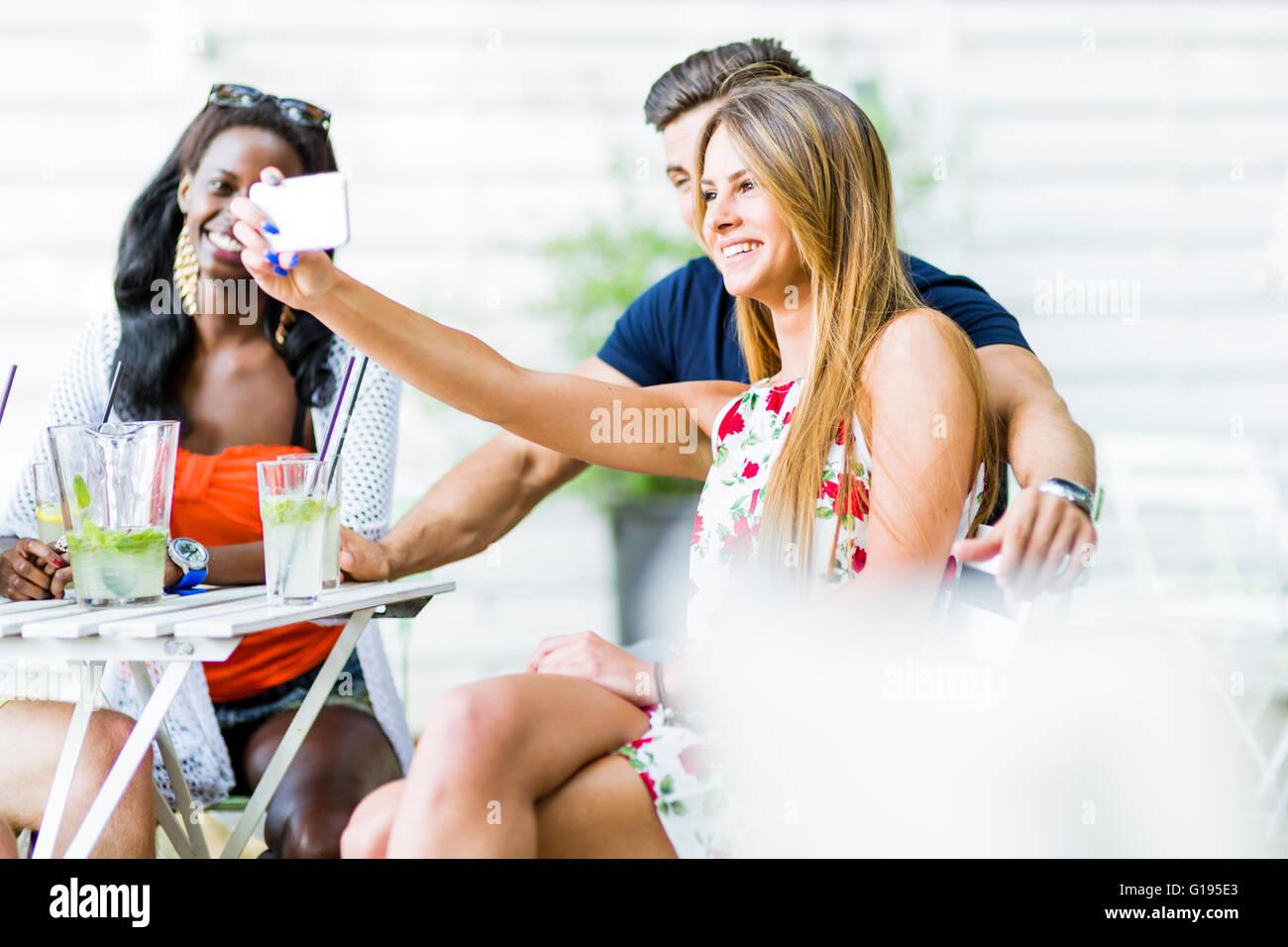 Un groupe d'amis assis une table et de parler en souriant tout en prenant vos autoportraits sur une chaude journée Photo Stock