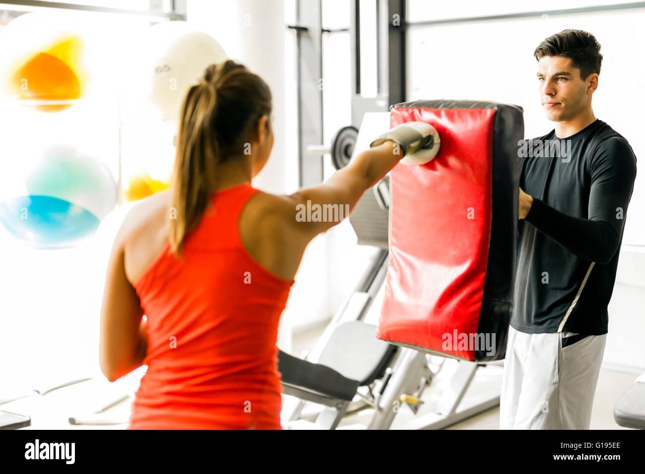 Jeune femme la boxe et la formation dans une salle de sport Photo Stock
