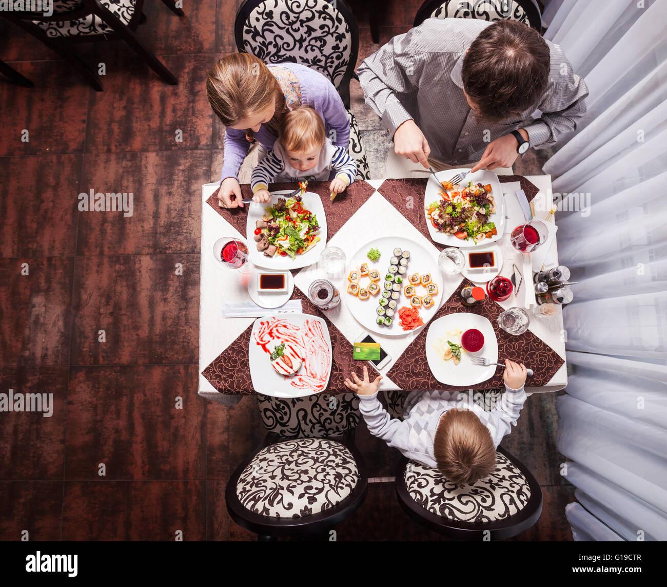 Famille de quatre personnes ayant délicieux repas dans un restaurant Photo Stock