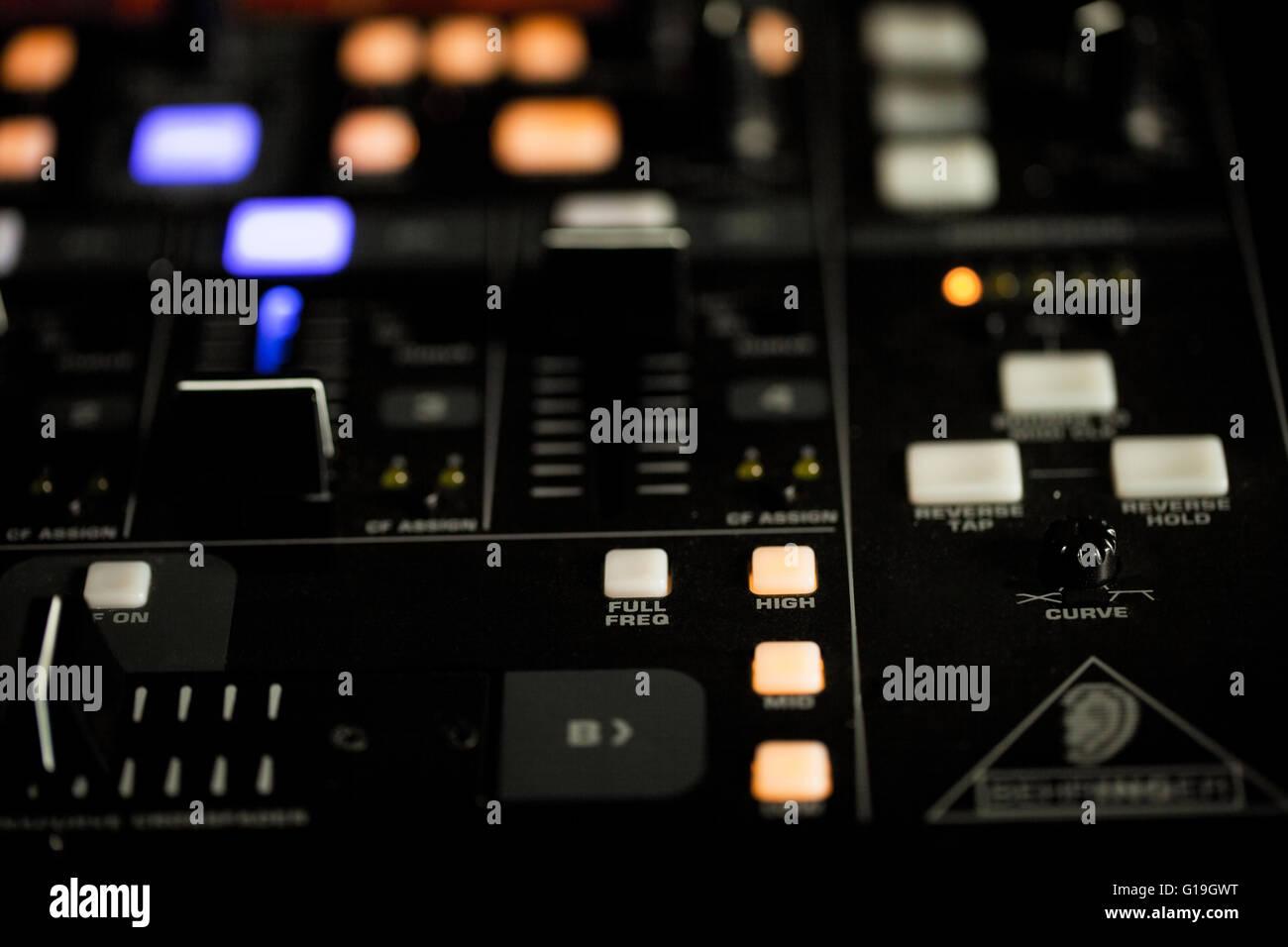Des feux allumés sur la console d'une platine DJ la nuit pour le mélange et l'effacement de la musique enregistrée dans une discothèque ou boîte de nuit Banque D'Images