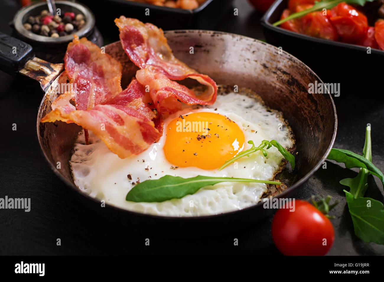 Petit-déjeuner anglais - œuf frit, haricots, tomates, champignons, bacon et pain grillé Photo Stock