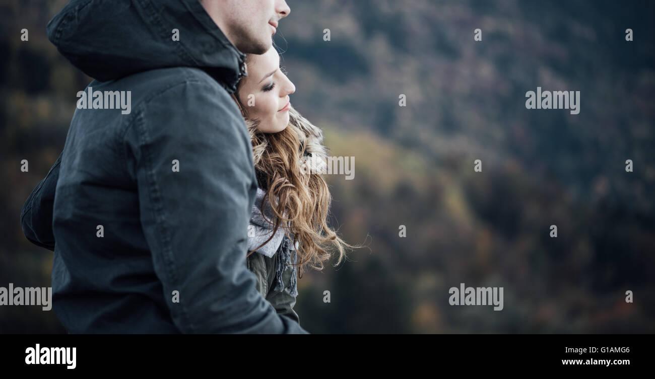 Jeune couple romantique en hiver, ils sont assis ensemble, elle est appuyée sur l'épaule de son petit Photo Stock