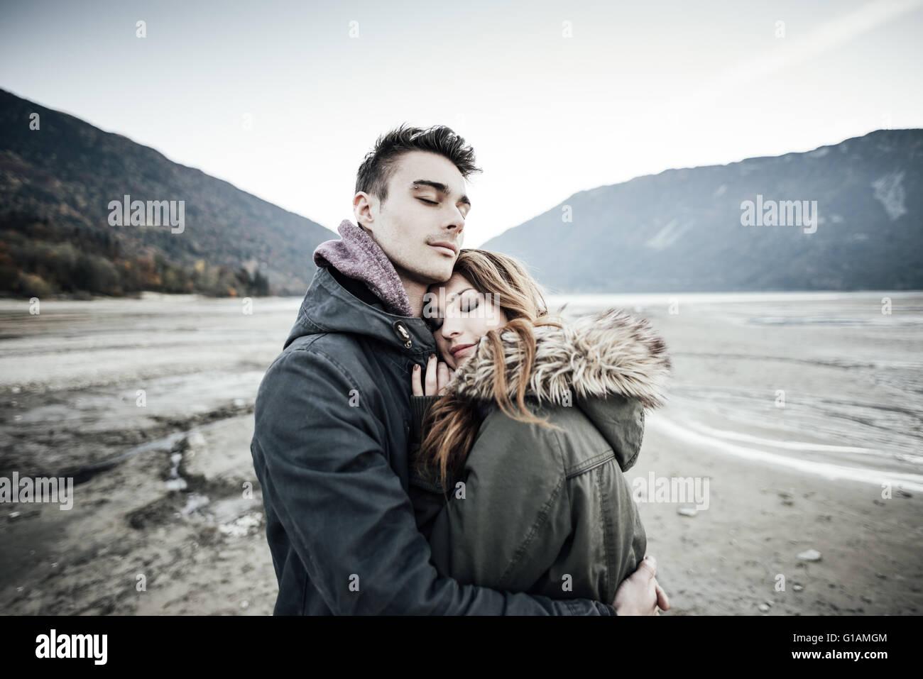 Jeune couple aimant s'étreindre, lac et montagnes en arrière-plan, l'amour et la romance concept Photo Stock