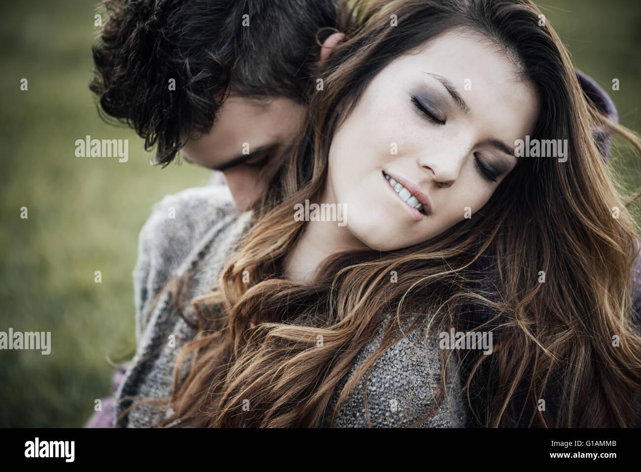 Couple romantique en plein air, ils sont assis sur l'herbe et s'étreindre, il est mordant sa lèvre Photo Stock