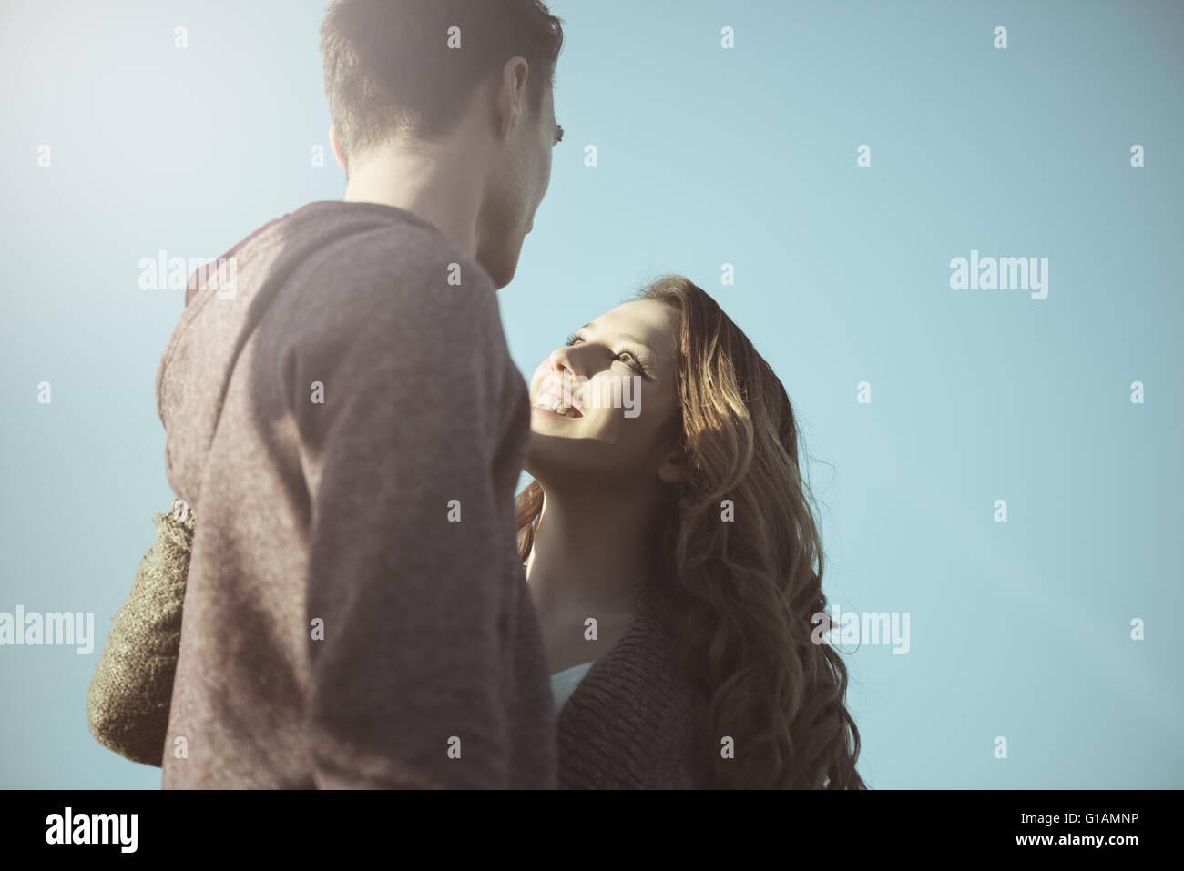 Les jeunes adolescents romantique à regarder les uns les autres contre le ciel bleu, l'amour et les rapports Photo Stock