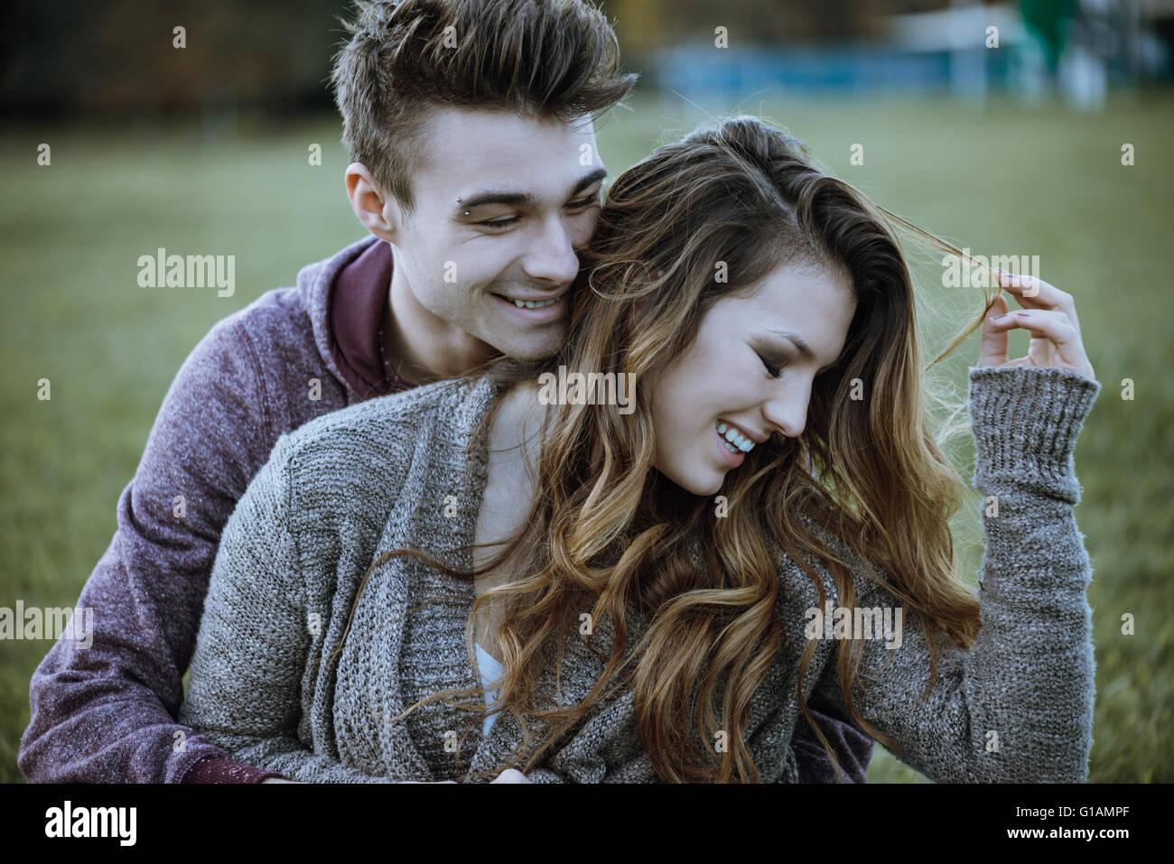 Jeune couple ludique assis sur l'herbe et s'étreindre, ils rient et profiter de Photo Stock