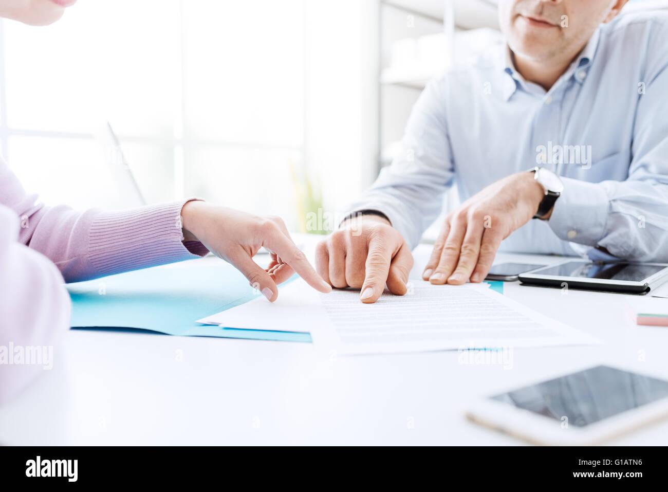 Les gens d'affaires la négociation d'un contrat, qu'ils pointent sur un document et discuter ensemble Photo Stock