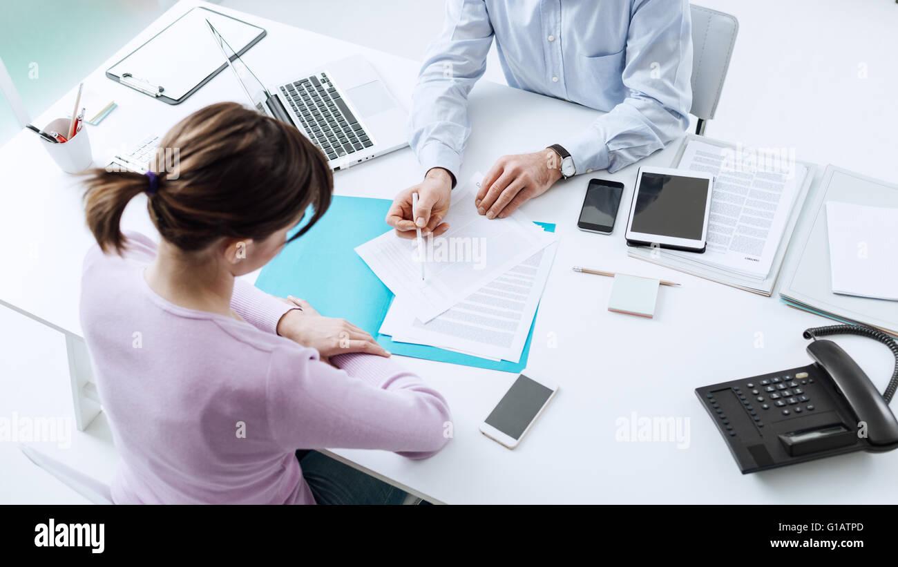 Rencontre avec un conseiller client dans son bureau, il est l'explication d'un document contractuel et de Photo Stock