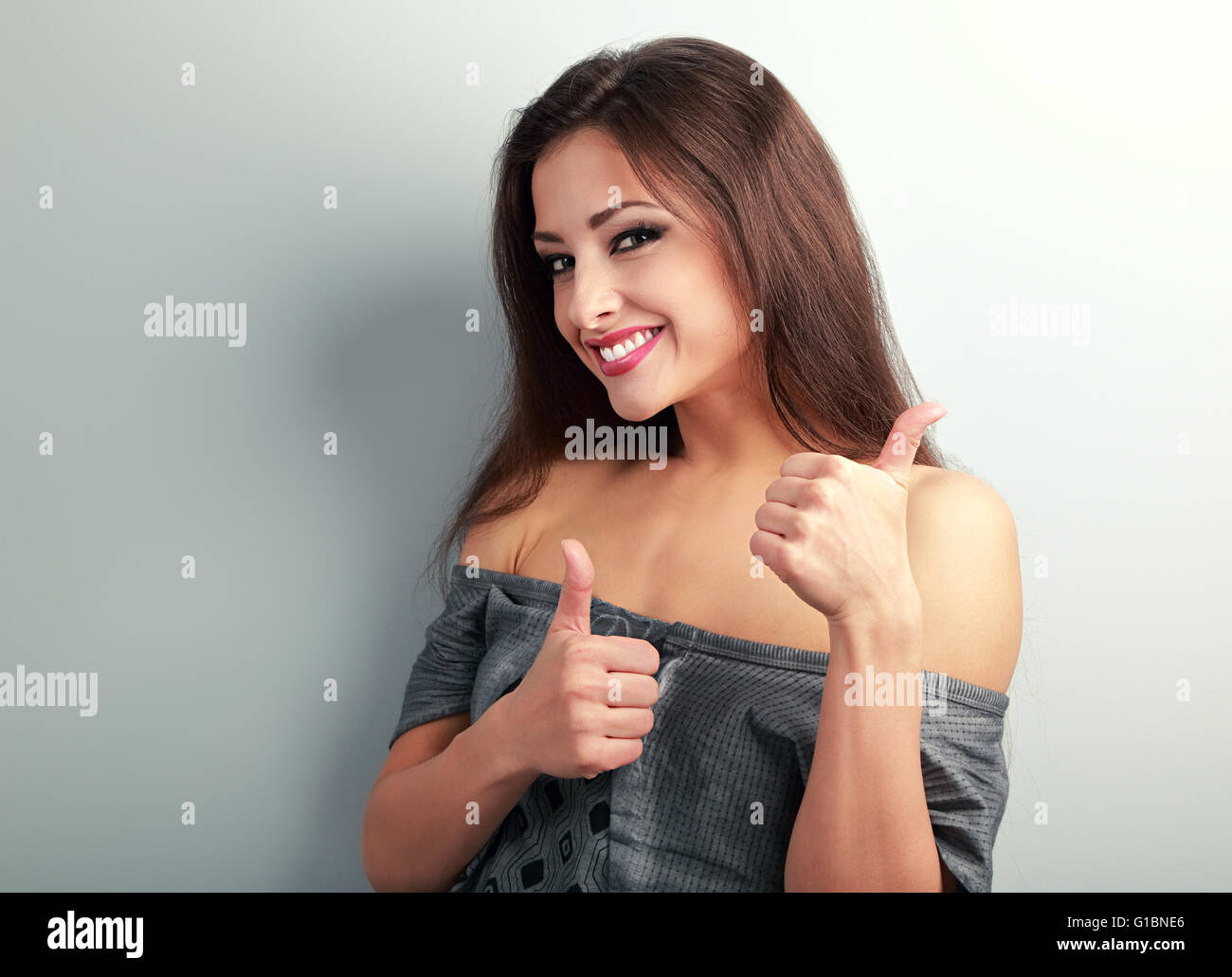 Professionnels optimistes brunette woman showing thumb up sign on blue background Photo Stock