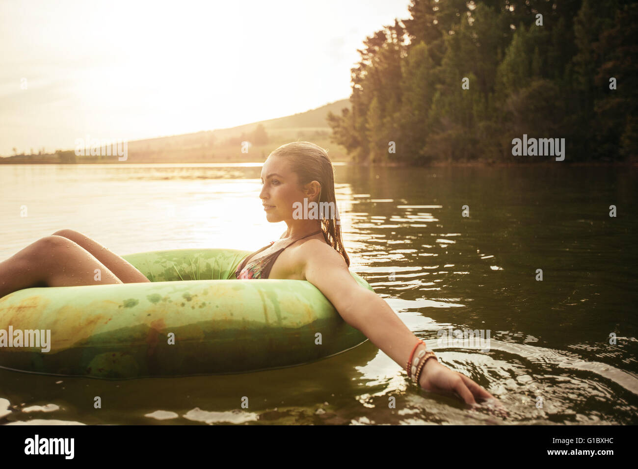 Side portrait of young woman in lake sur anneau gonflable. Woman relaxing dans l'eau un jour d'été. Photo Stock