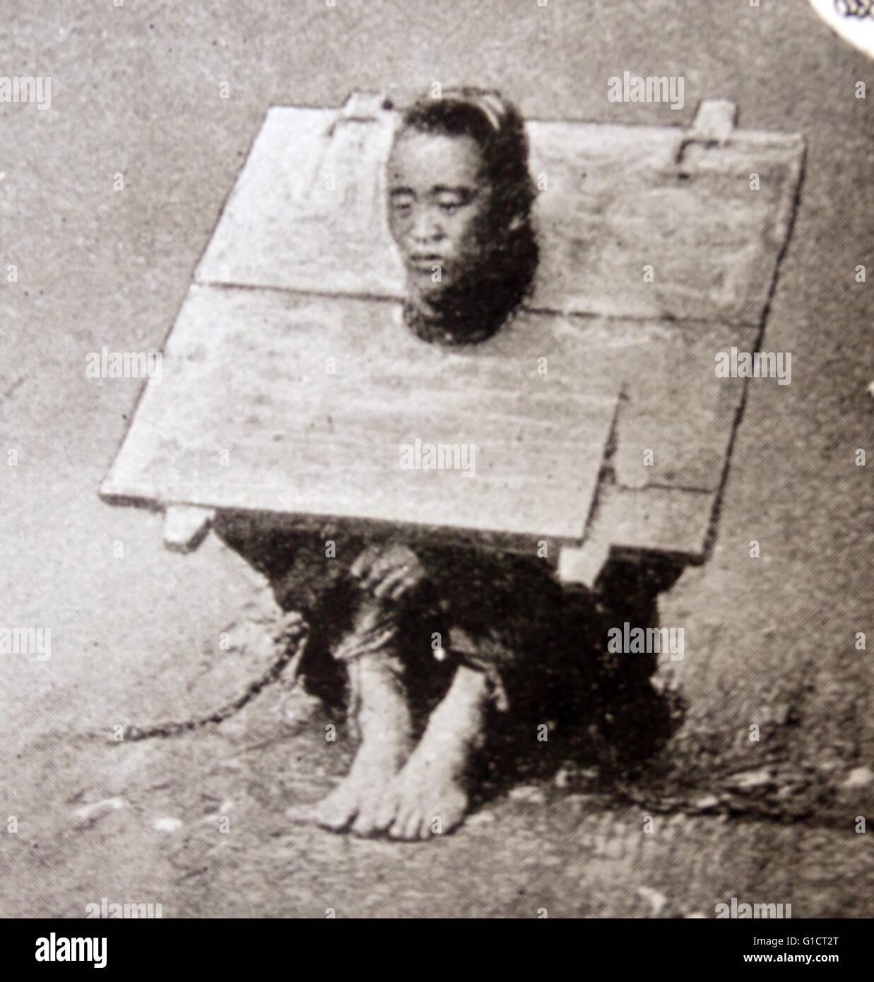 Criminel chinois ou esclave d'obligations dans une chape en bois pour sécuriser sa captivité vers Photo Stock