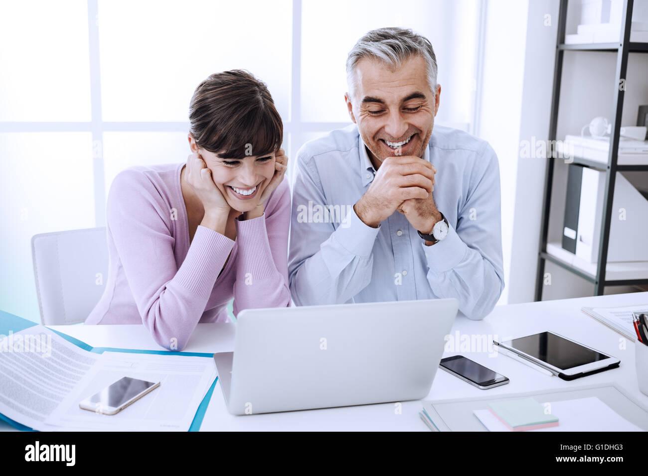 Les employés de bureau assis à un bureau et surfer sur le web avec un ordinateur portable, ils profitent Photo Stock