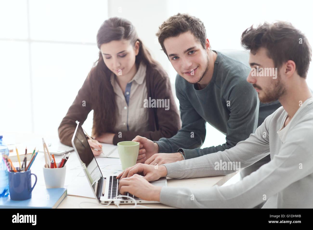 Groupe d'étudiants du collège à 24 en utilisant un ordinateur portable, la mise en réseau Photo Stock