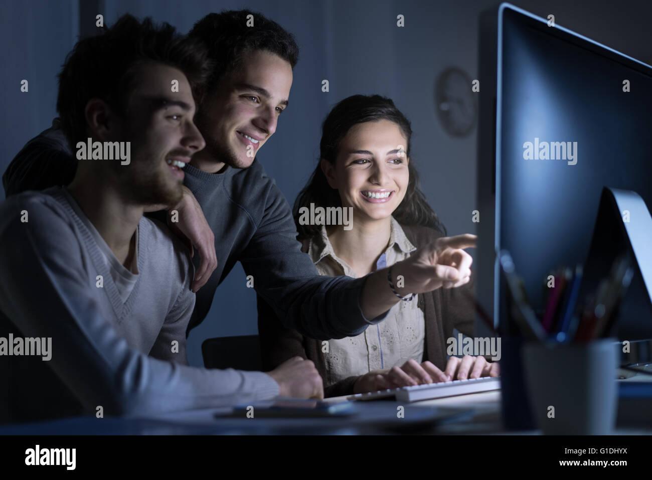Smiling students connexion à internet avec un ordinateur, ils sont la mise en réseau et de consultation Photo Stock