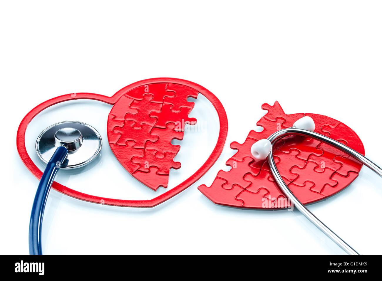 La maladie de coeur, en forme de cœur de Split casse-tête avec stéthoscope sur fond blanc Photo Stock
