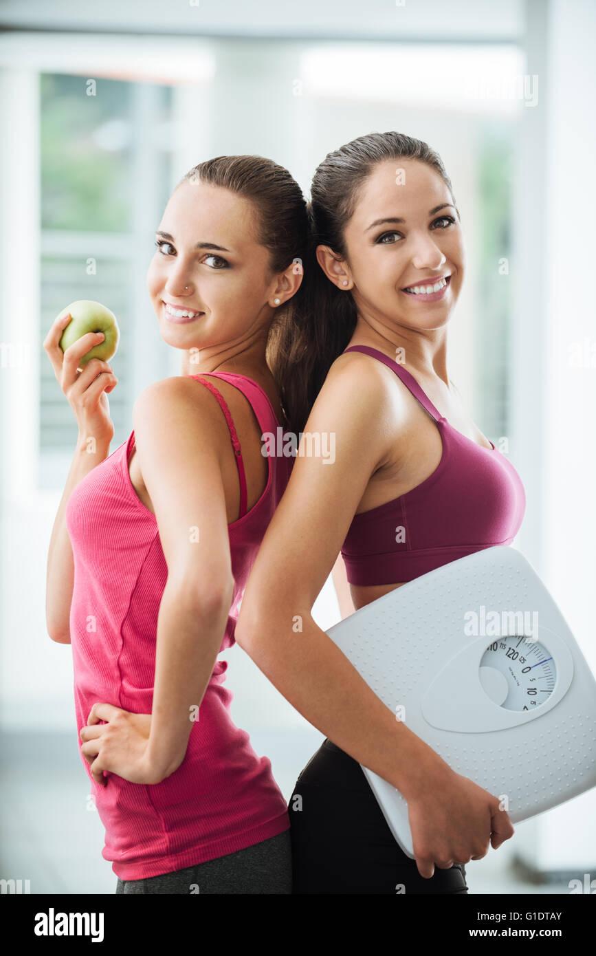 Teenage girl friends tenant une pomme et une échelle, ils posent et smiling at camera, fitness et perte de poids Banque D'Images