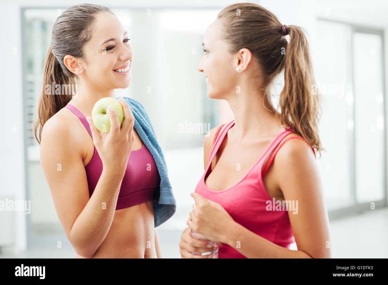 Belles jeunes filles dans la salle de sport jouissant et parler ensemble pendant une séance de pause, l'un Photo Stock