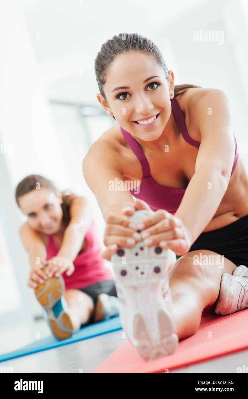 Souriante jeune femme à la salle de sport de faire un exercice d'étirement des jambes sur une natte, Photo Stock