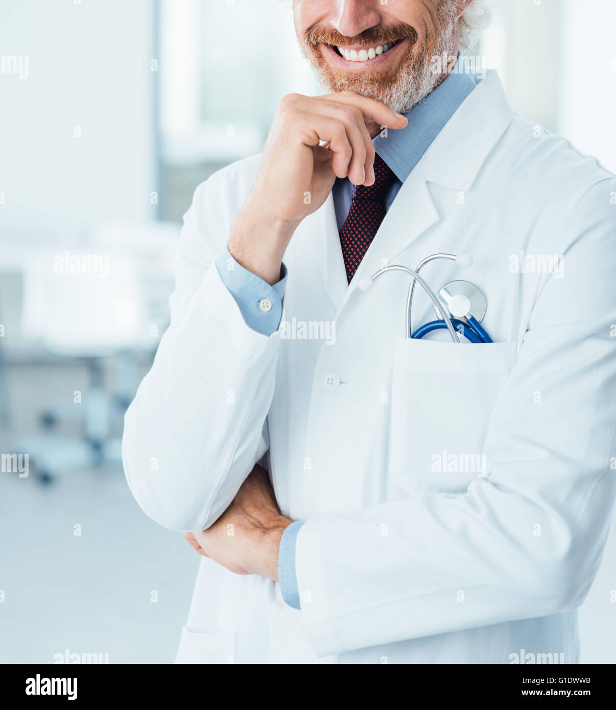 Professional doctor posing at hospital and smiling at camera with hand on chin Photo Stock