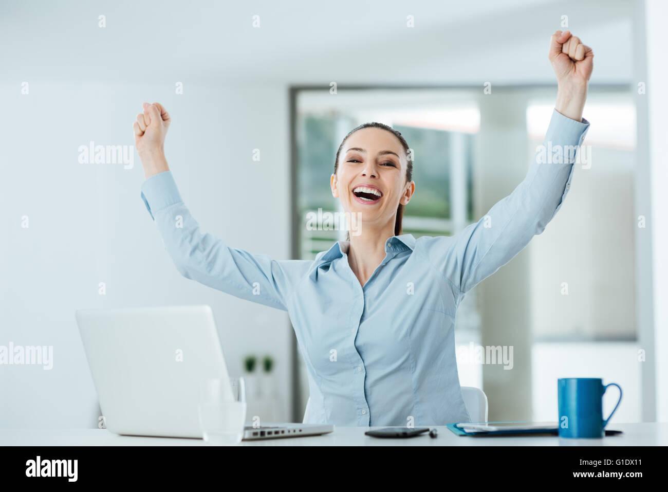 Cheerful businesswoman réussie avec les poings soulevées sitting at Office 24, réalisation et concept Photo Stock