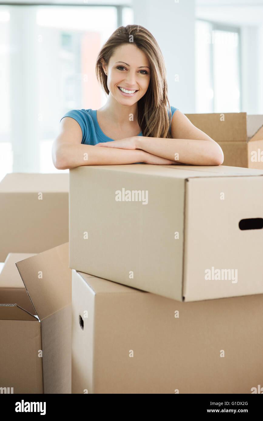 Souriante jeune femme déménagement dans sa nouvelle maison et s'appuyant sur une boîte en carton Banque D'Images