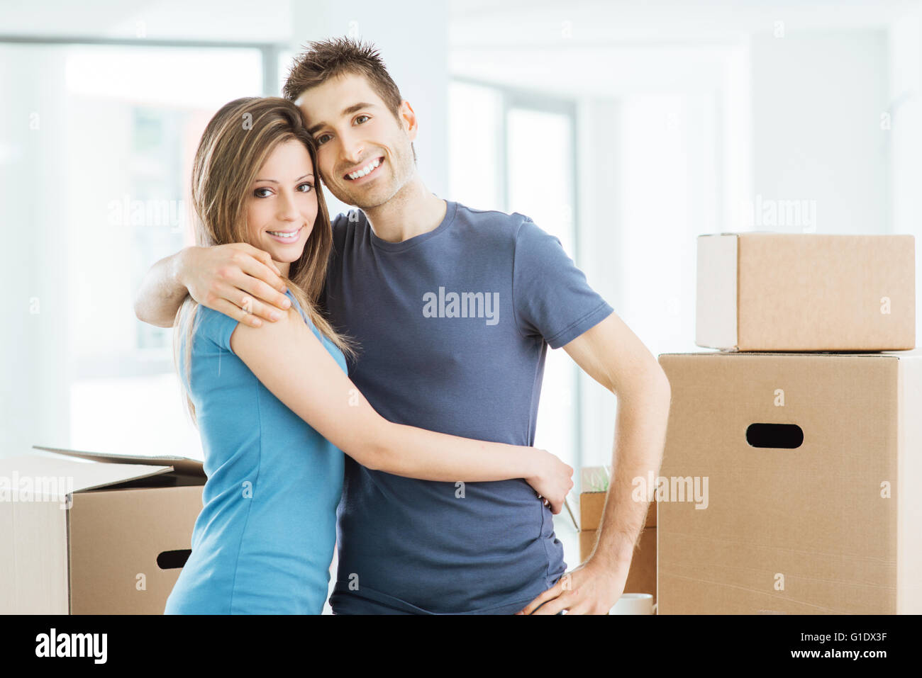 Young happy couple hugging in their new house and smiling at camera Photo Stock